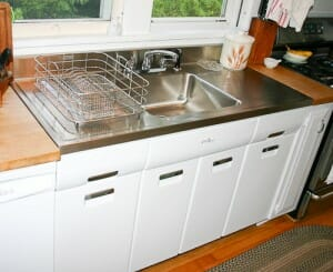 2011 elkay stainless steel drainboard sink installed onto a vintage steel kitchen cabinet