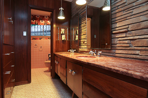 pink bathroom with dark wood paneling and stone wall