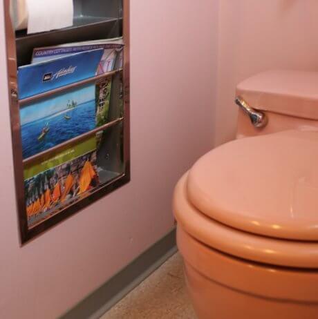 pink bathroom with recessed metal magazine rack