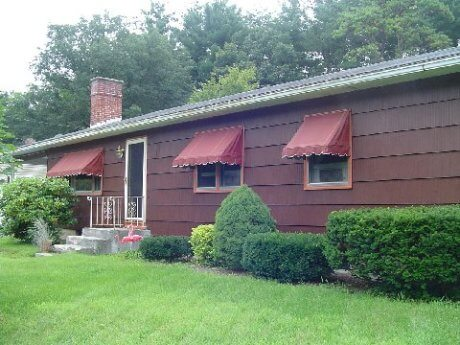 ranch house front with awnings
