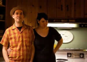 kelly and mark in their knotty pine kitchen