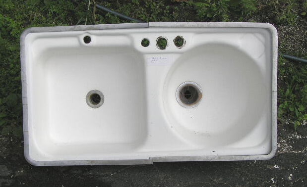 A vintage kitchen sink with one square bowl and one round bowl ...
