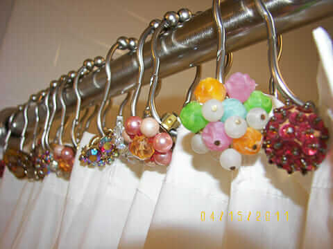 vintage earrings used to decorate shower curtain rods