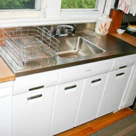 2011 elkay stainless steel drainboard sink installed onto a vintage steel kitchen cabinet
