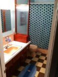 Checkerboards, polka dots & surfer decor perk up the pink bathroom at Joe's house