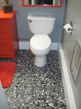 Vintage pebble floor tile launches Tex's gray, black, orange and white bathroom remodel
