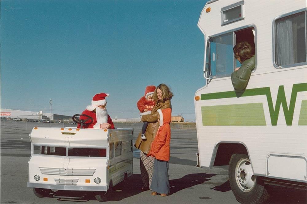 Santa in mini Winnebago car from the 1960s