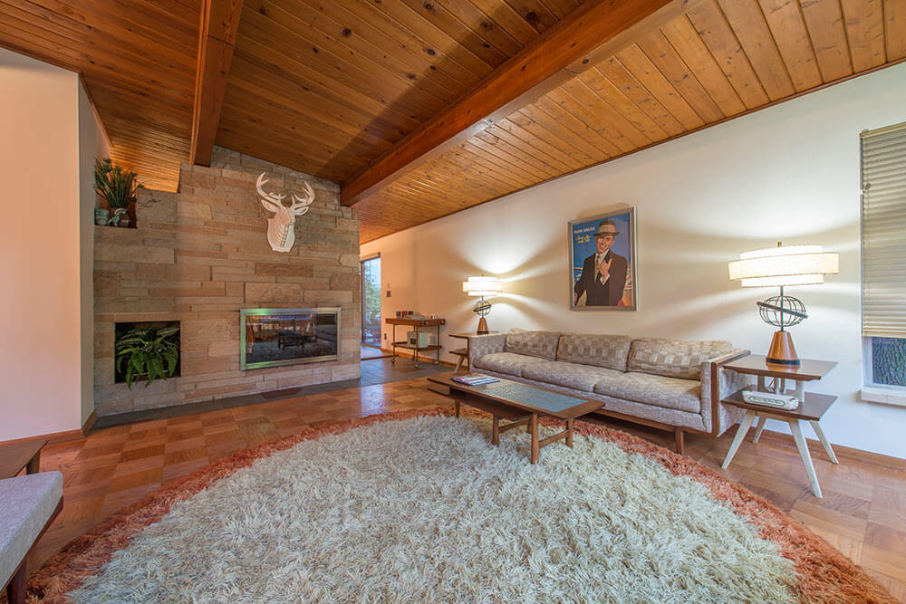 living room with stone fireplace wall and wood paneled ceiling