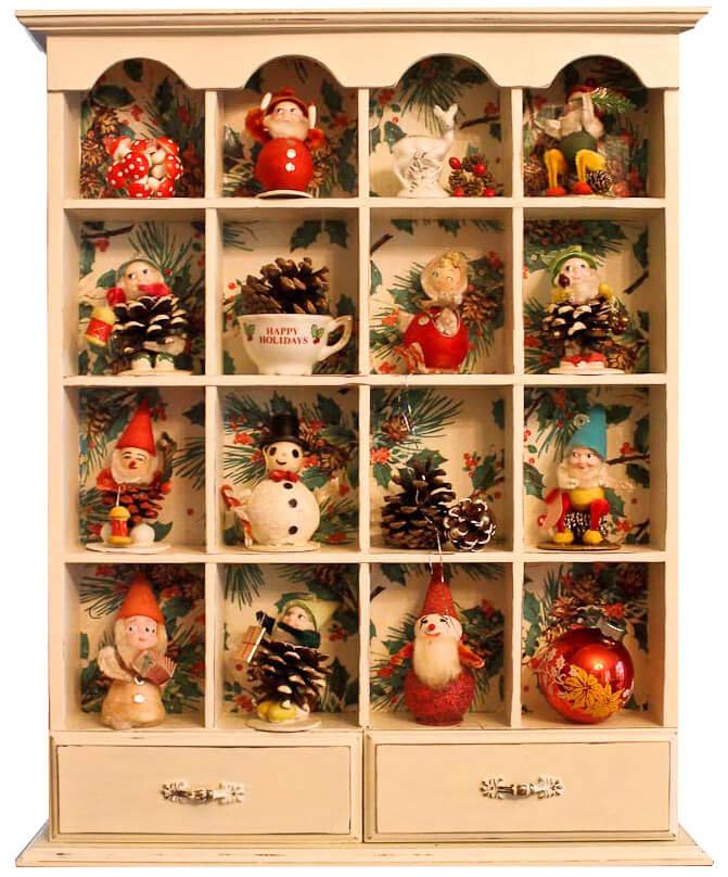 pinecone elves in their own shelf condo