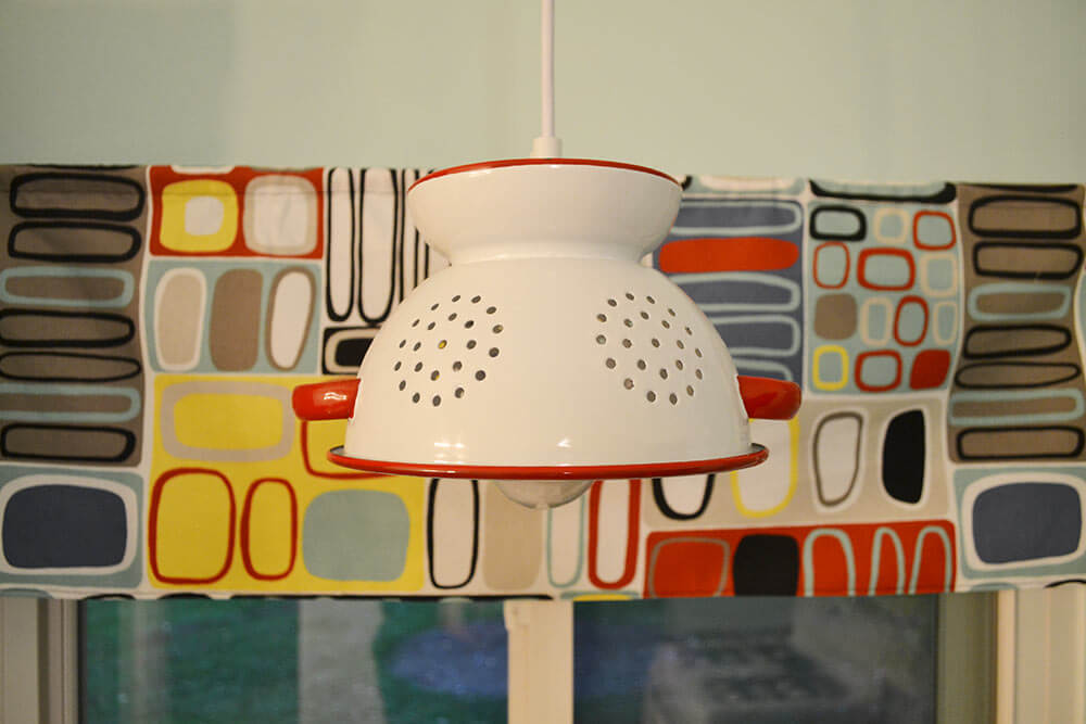 vintage colander used to make a pendant light in the kitchen