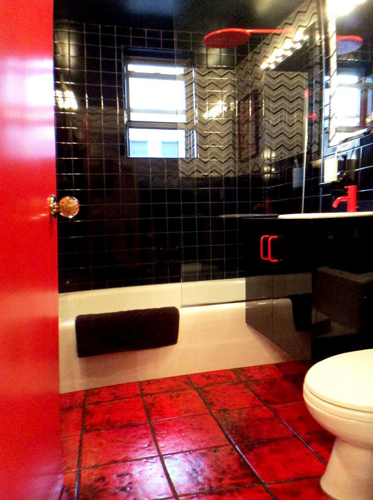 bathroom with black tile and red vola faucet