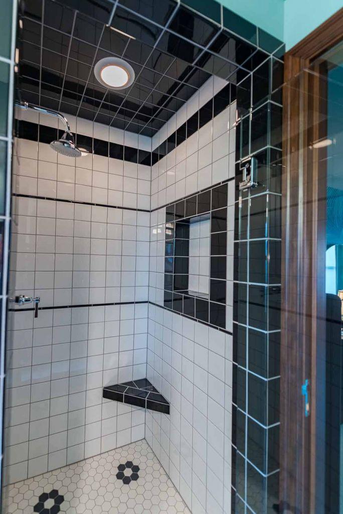 white tile shower with black trim