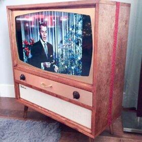 mid century tv box that holds a modern flatscreen tv