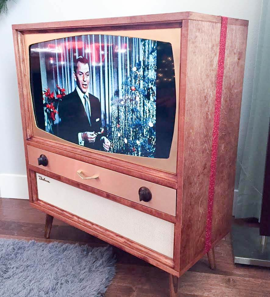 mid century tv box that holds a modern flatscreen tv