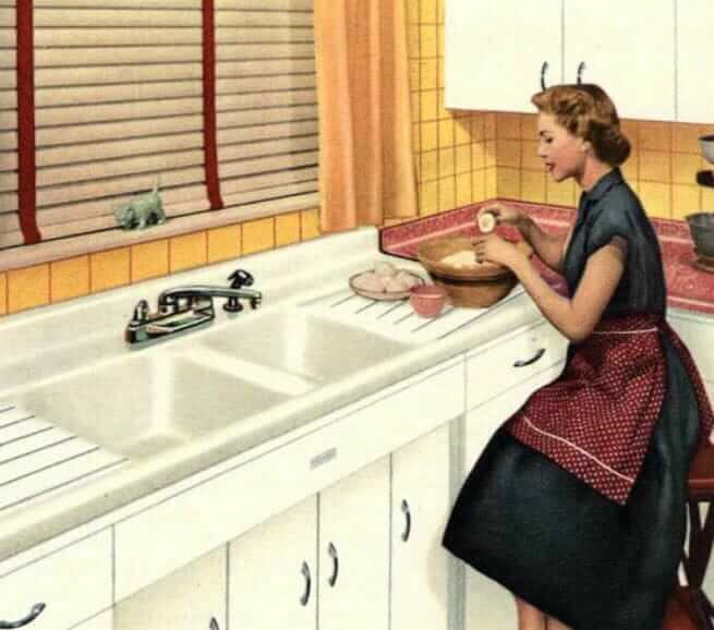 homemaker working at a double sink in her 1950s kitchen