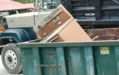brown vintage stove in dumpster